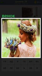 на голове девушке лежит венок из цветов и в руках букет