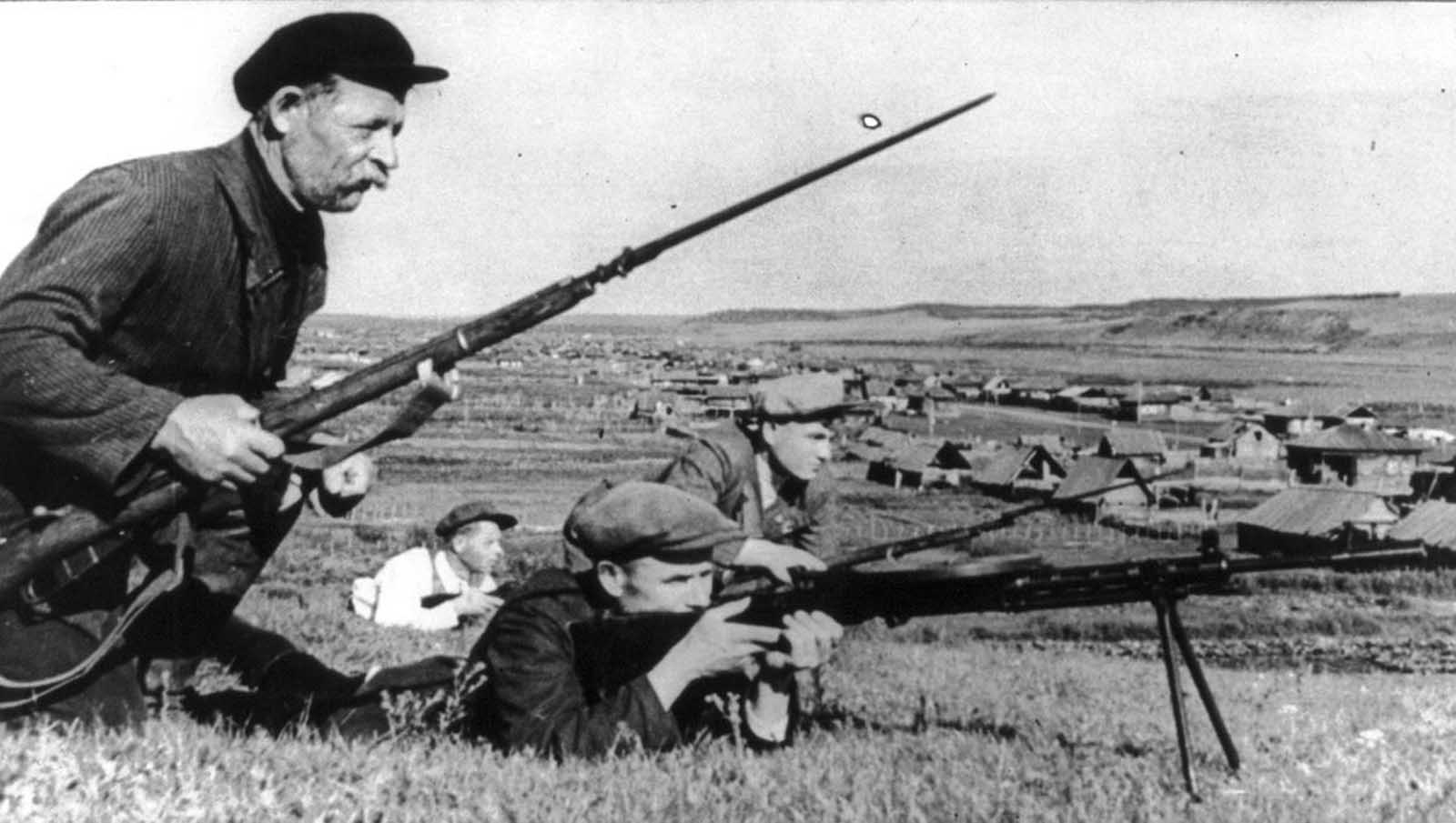 Rapidly advancing German forces encountered serious guerrilla resistance behind their front lines. Here, four guerrillas with fixed bayonets and a small machine gun are seen in action, near a small village.