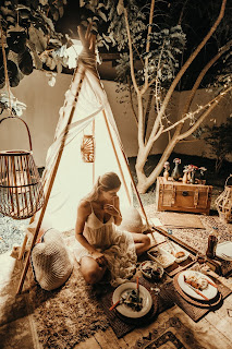 A sepia-toned picture of a woman sitting on the ground in a small teepee with plates of food on the rug around her.