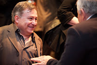 A photo of Simon, who is short statured, talking to someone. Simon is in a brown suit and shirt and smiling.
