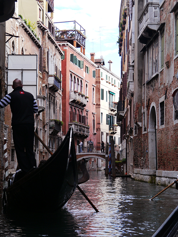 Gondolier steering a gondola down a narrow canal in Venice, Italy