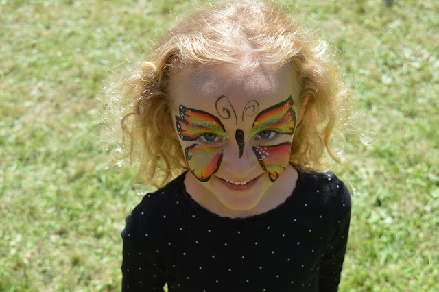 Molly in the sunshine with a butterfly face paint.
