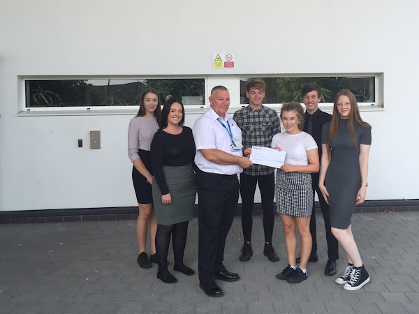 Sir Robert Woodard Academy presents a cheque to Harvey's gang