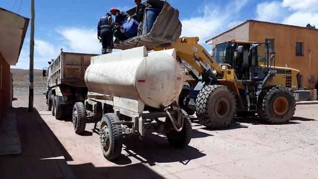 Um unsere Erdtrassen herzurichten, muss das Bürgermeisteramt viele Tausend Liter Diesel bereitstellen. Da wir keine Tankstelle haben, wird der Treibstoff per LKW zuerst einmal aus Uyuni in sechs Stunden in Fässern angekarrt. Dann werden sie vor dem Bürgermeisteramt abgeladen, was ohne Kran recht schwierig ist. Einige alte Autoreifen werden aufgeschichtet, auf die man dann die 200 Liter Fässer von der Ladefläche des LKW fallen lässt. Wenn dann die Baumaschinen auftauchen, werden immer 3 Fässer auf die Schaufel des Baggers geladen. Diese werden dann zur Zisterne gefahren und die 3 Arbeiter saugen im Schlauch den Treibstoff an, der dann in die Zisterne hineinläuft. Gewusst wie, könnte man sagen.