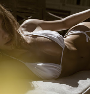 blonde escort lying on bed wearing white bikini