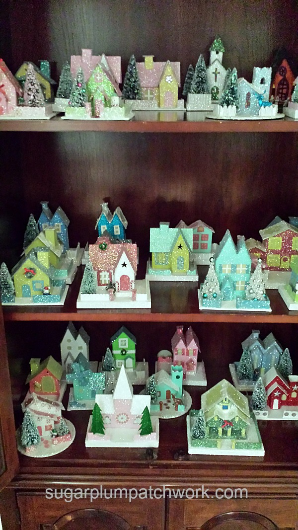 Glitter houses on curio cabinet shelves