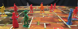 A perspective shot of the board mid-game. The board, representing various rooms in the palace of the Louvre, stretches out into the background of the photo. The four musketeer figurines, one each in blue, green, orange, and yellow, are in different rooms of the palace. The green one, in the foreground, occupies the same room as Milady D'Winter, a red figurine holding up a goblet. The yellow one, in the left midground, faces Rochefort, also in red, who holds a pistol. The blue one and the orange one are facing off against various palace guards, red figurines with swords that are scattered about the board. In the background, the grey figurine representing Queen Anne, can be seen on the far edge of the board which represents the throne room.