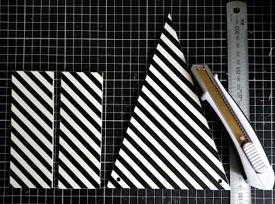 Two rectangular and one bunting-shaped pieces of plywood printed with black and white stripes,laid out on a cutting mat, along with a metal ruler and a utility knife.