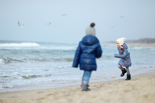 Two bundled up children playing on a wintery beach