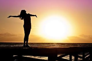 Silueta de una chica subida a un muelle de madera en un atardecer, mientras que abre los brazos y dejo que el sol y el viento le de.