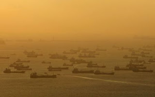Shipping vessels and oil tankers line up on the eastern coast of Singapore in this July 22, 2015. (Credit: Reuters/Edgar Su/Files) Click to Enlarge.
