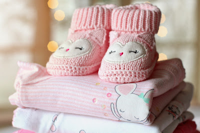 Folded pink and white baby outfits with a pair of pink bootees sitting on top