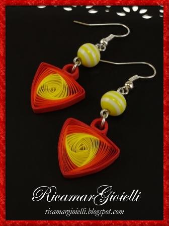 Orecchini realizzati in quilling a forma di vortice triangolare e decorati con le perle