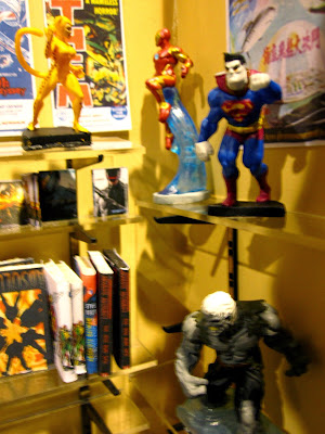Interior view of a modern dolls' house miniature comic book shop, showing the metal shelving brackets