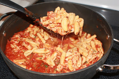 this is a homemade cavatelli Italian pasta in a large round pot, Italian dish with Traditional homemade Italian sauce on top and a serving spoon in it.