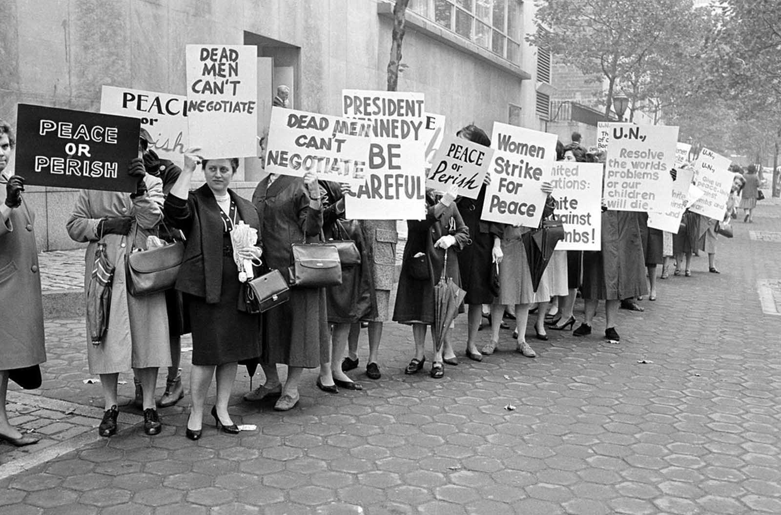 Picketers representing an organization known as Women Strike for Peace carry placards outside the United Nations headquarters in New York City, where the U.N. Security Council considers the Cuban missile crisis in a special meeting, on October 23, 1962.