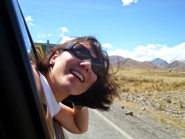 Una mujer sonríe feliz dentro de un carro