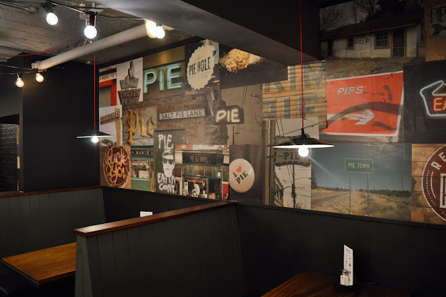 a selection of seating and a wall with lots of posters on the wall.