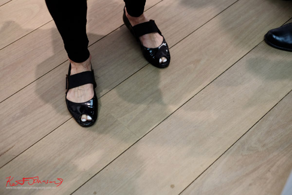 Black patent open toe woman's shoe, white toe nail polish.