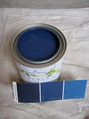 Can of Benjamin Moore Deep Royal blue with paint swatches