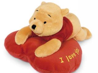 Winnie the pooh en cojín rojo en forma de corazón para el día del Amor