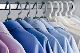An array of dress shirts in order from darkest to lightest