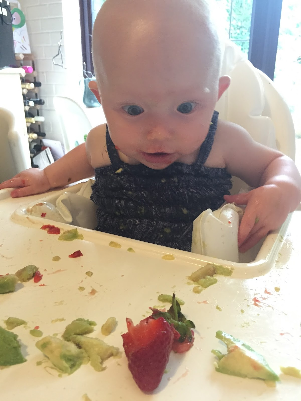 A baby looks in wonder at a partially munched strawberry on her high chair tray