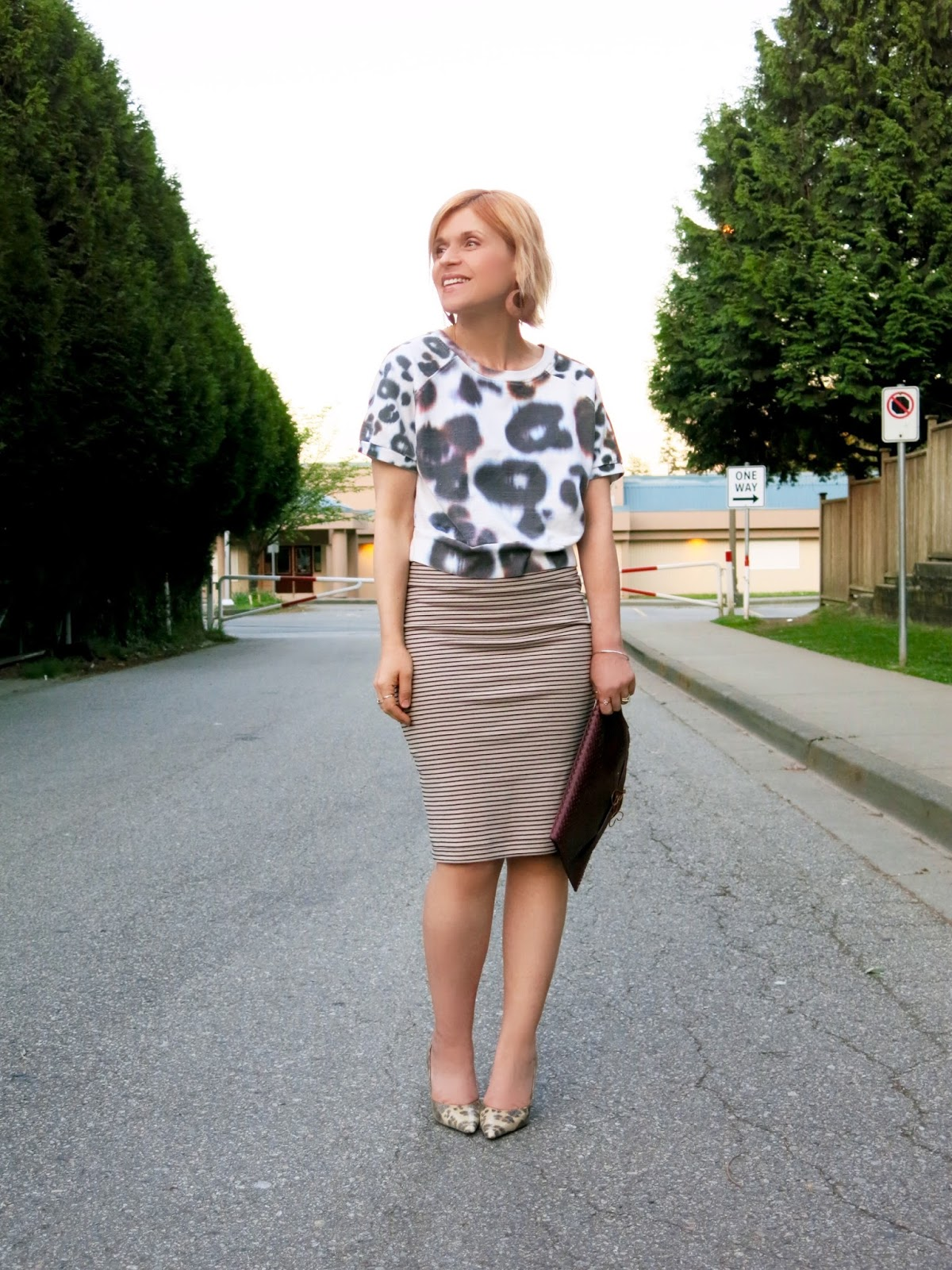 styling a striped pencil skirt with a cropped sweatshirt, faux-reptile pumps, and envelope clutch