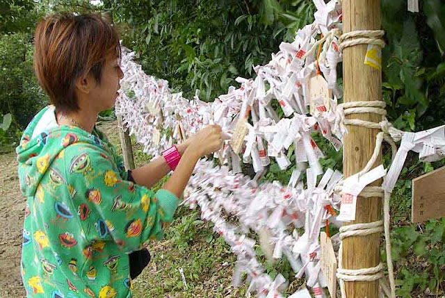 Girl tying a bad New Year's fortune to fence