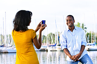 Photo of an African-American Woman Taking a Picture of an African-American Man While on Holiday