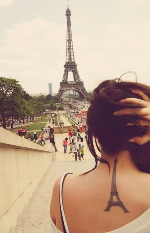 Chica tatuada frente a la torre eiffel