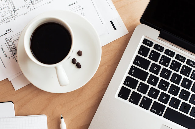 stock flat lay image of a coffee cup, laptop and business papers on a desk
