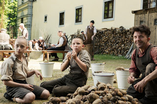 Two boys with shaved heads(Niklas Post and Ivo Pietzcker) and a man (David Bennent) sit outdoors by a pile of potatoes looking amused and shocked. Behind them, men are making baskets.  Courtesy of StudioCanal.