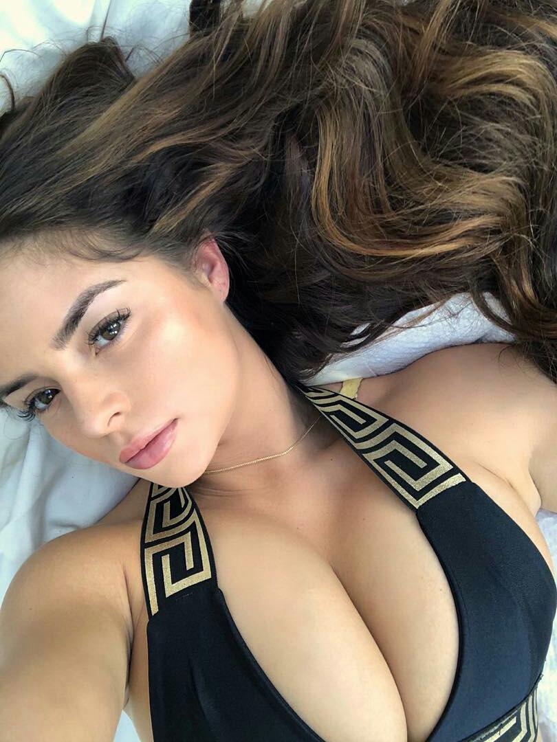 Demi Rose lying on a bed taking selfie