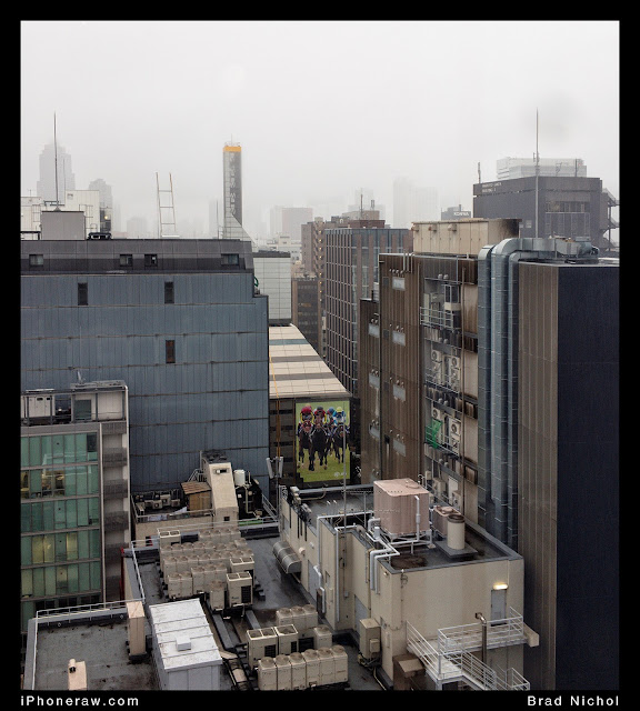 Ginza from 9th floor in Typhoon with rain showing tops of buildings and foggy sky.