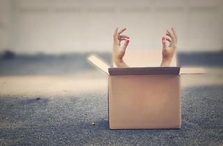 Manos saliendo de una caja de cartón