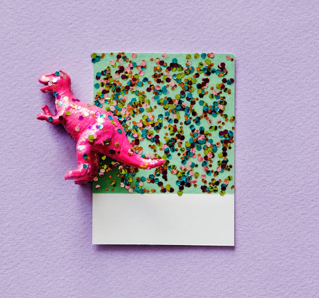 Pink Dinosaur toy and craft paper covered with glitter confetti dots