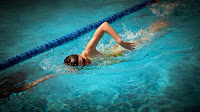 Image of a swimmer doing front crawl drills in a swimming pool lane