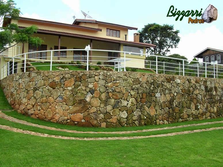 Calçamento de pedra rústica na entrada da residência com faixa de 70 cm de largura com a execução do muro de pedra rústica e construção da piscina com a construção da residência.