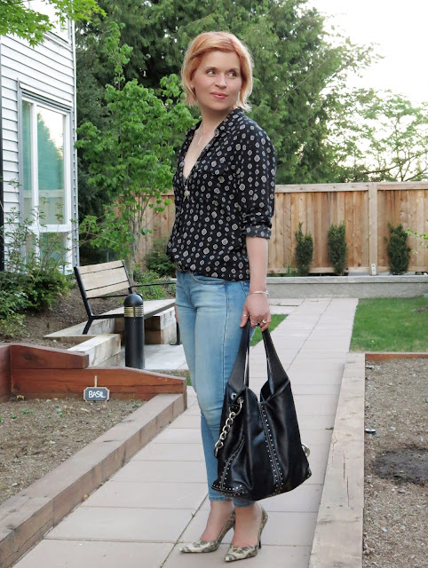 styling a black patterned shirt with faded skinny jeans, animal-print pumps, and a Michael Kors studded bag