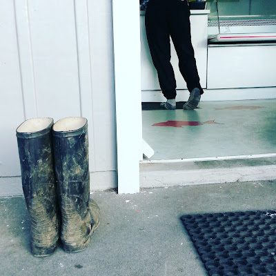 A pair of muddy gumboots outside a fish and chip shop. Inside, the owner of the boots is ordering at the counter.