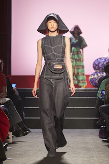 A woman with short black hair in a bob style hair style wearing a short plum coloured top that comes above the waist with a silver half circle design all over it with black denim pants on a long rectangular catwalk on a bright background