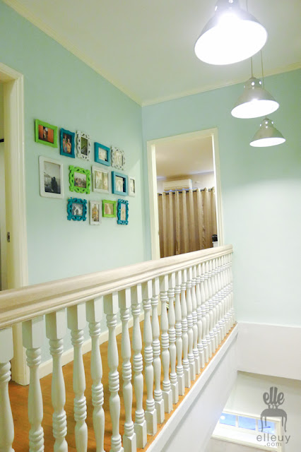 light blue hallway with colorful wall frames and white wood railing