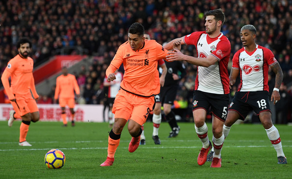 Roberto Firmino of Liverpool is challenged by Jack Stephens of Southampton during the Premier League match between Southampton and Liverpool at St Mary's Stadium on February 11, 2018 in Southampton, England.
