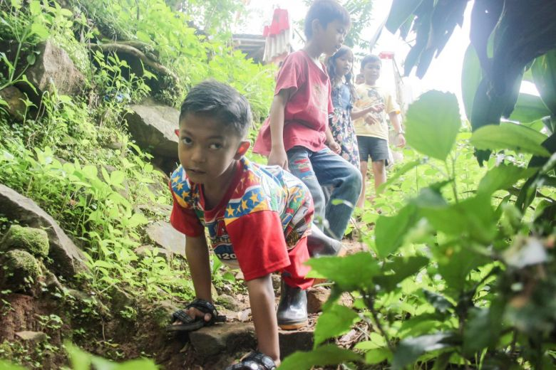 Mukhlis Abdul Holik walks using his hands while playing with his friends at Sekarwangi village, in Sukabumi, West Java province, on Dec 15, 2018.