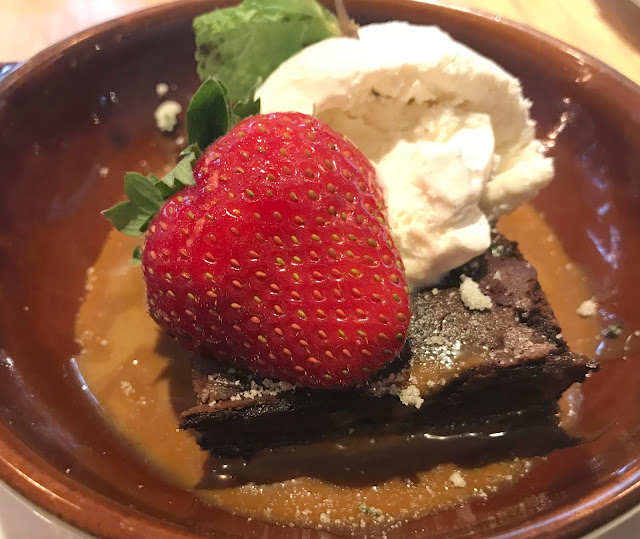 chocolate brownie with run caramel sauce, ice cream and strawberry