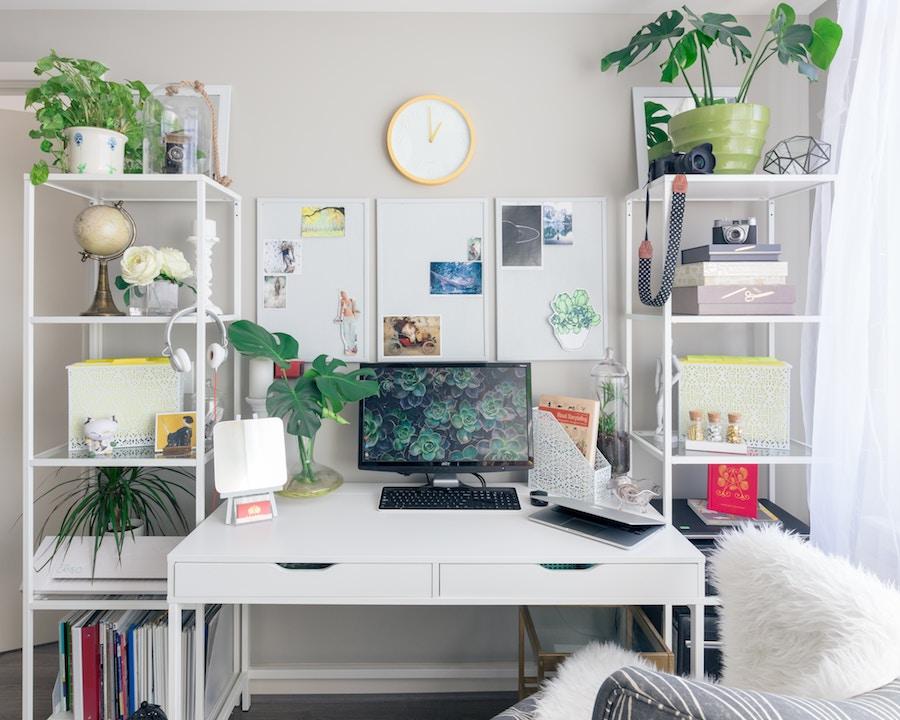 zona de trabajo en un piso pequeño  con mesa y dos estanterías a los lados