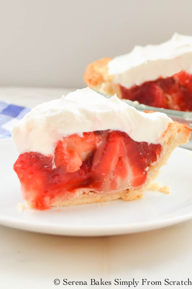 A slice of Strawberry Pie from scratch in a flaky pastry crust covered with whipped cream on a white plate with a sliced whole strawberry pie in the background.