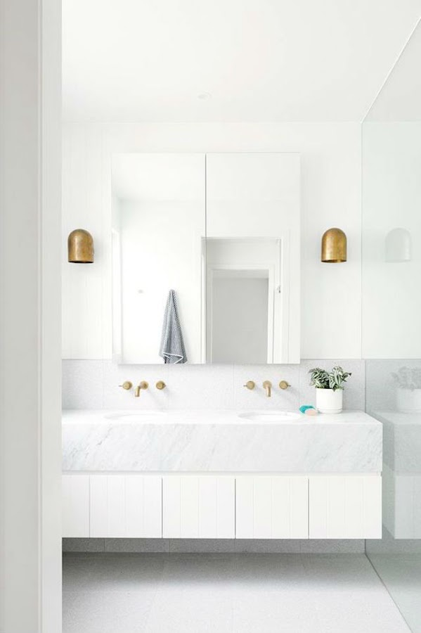 Baño con paredes y suelo de mármol y detalles dorados en grifos y apliques de pared