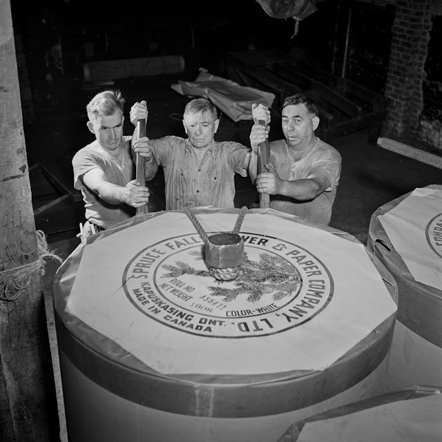 In the reel room, pressmen transport a 1608-pound paper reel to the presses. The reel has enough for about 1300 newspapers.
